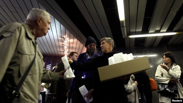 A leader of ANO 2011 movement Andrej Babis (C) hands out donuts during an election campaign rally at a subway station in Prague, Oct. 23, 2013.