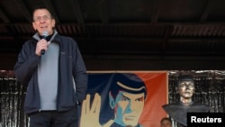 FILE - With a likeness of his Vulcan character, Mr. Spock, in the background, Leonard Nimoy speaks to the residents of the town of Vulcan, Alberta, April 23, 2010.