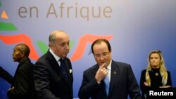 FILE - French President Francois Hollande (R) and Foreign Minister Laurent Fabius attend the opening session of the Elysee Summit for Peace and Security in Africa at the Elysee Palace, in Paris, Dec. 6, 2013.