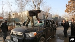 An Afghan driver removes a broken windshield of his car following the Friday's suicide attack and shooting in Kabul, Afghanistan, Saturday, Jan. 18, 2014.