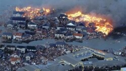 Houses burn in a flooded area of Natori City in northern Japan after the earthquake and tsunami on Friday