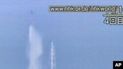 This screengrab taken off Japanese national broadcaster NHK shows a Japanese military twin-rotor cargo helicopter dumping water onto reactor no. 3 at the stricken Fukushima nuclear power plant on March 17, 2011.
