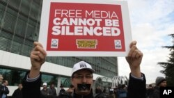 一名男子手持標語牌抗議土耳其警方對土耳其境內發行量最大的報刊的辦公地點進行了突擊。