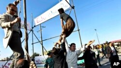 FILE - Men are trying to prevent the execution of convict pardoned by the family of a policeman he was convicted of killing, in Mashhad, northeastern Iran, May 8, 2013.
