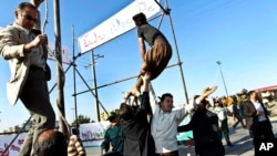 Men prevent execution of convict after being pardoned by family of policeman he murdered, Mashhad, northeastern Iran, May 8, 2013.