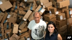 Catholic Charities of the Rio Grande Valley staffer Eli Fernandez and volunteer Natalie Montelongo stand by a pile of unsorted Amazon boxes packed with donations in McAllen, Texas, June 24, 2018.