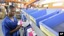 A worker looks at the stock of medicine in the Pharmacie de la Sante Publique (Public Health Medicine) warehouse in Abidjan, March 17, 2011