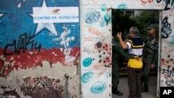 委内瑞拉周日举行地方选举,一名男子在首都加拉加斯的投票站前被警卫搜身。(2017年10月15日)