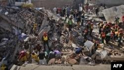 Nhân viên cứu hộ và cư dân đào bới trong đống đổ nát của tòa nhà bị sập tại Lahore, ngày 6/2/2012