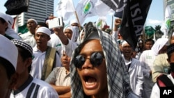 FILE - Members of the militant Islamic Defenders Front (FPI) shout slogan during a demontration in Jakarta, Indonesia.