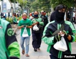 Pengemudi ojek online antre bantuan makanan gratis di tengah pandemi virus corona (COVID-19), di Jakarta, 17 April 2020. (Foto: Reuters)