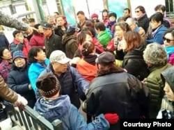 北京的野靖环(橘黄衣)在居委会附近被大批人围堵(网络图片)
