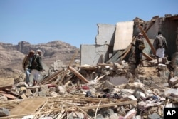FILE - People inspect the rubble of a house destroyed by a Saudi-led airstrike in the outskirts of Sana'a, Yemen, Feb. 16, 2017.
