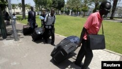 South Sudanese men carry luggage as they walk towards Tel Aviv's central bus station to board a bus to Ben Gurion airport, Israel, June 17, 2012.