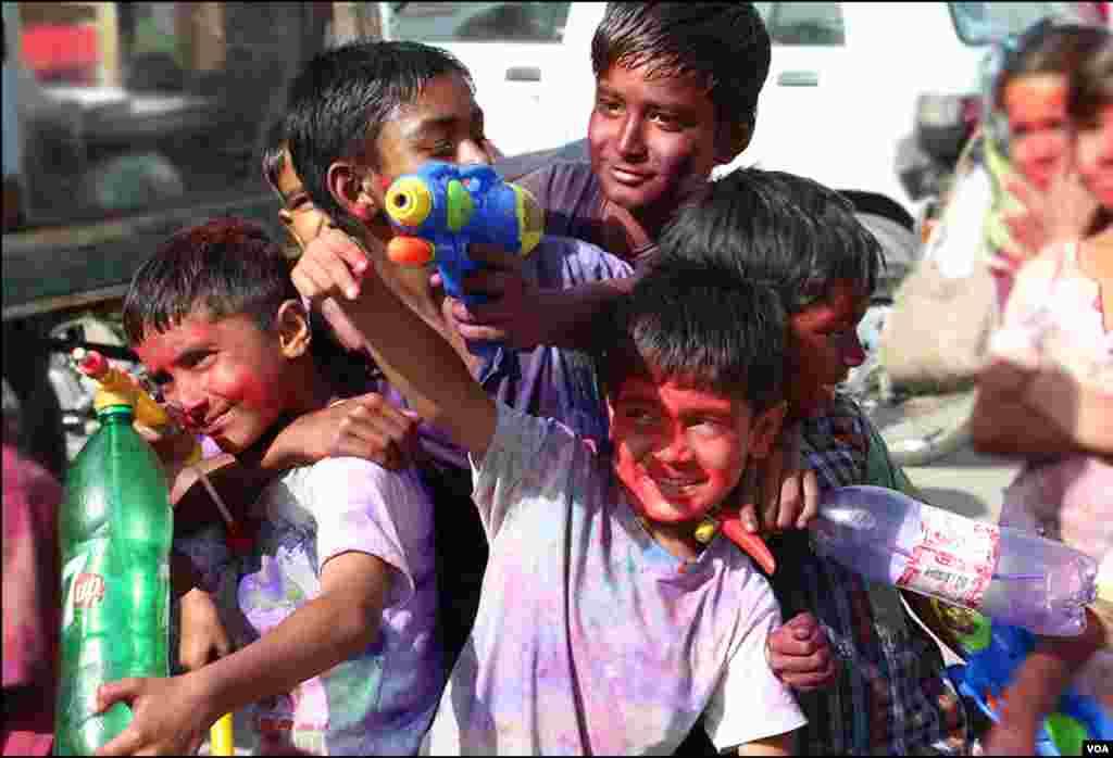 واٹر گن اور رنگوں کو بوتلوں میں بھر کر کھیلتے ہوئے بچے