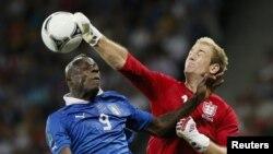 Joe Hart retire une balle au dessus de la tête de Mario Balotelli lors d'un match de l'euro 2012