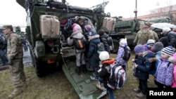 "Fighting in Ukraine has affected life there. Here, children wait in line to see a U.S. militiary vehicle during the ""Dragoon Ride"" military exercise in Prague, March 31, 2015. (FILE PHOTO)"