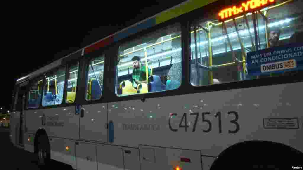 People are shown on an official media bus after its window was shattered while driving journalists to the Main Transport Mall from the Deodoro Stadium of the Rio 2016 Olympic Games in Rio de Janeiro, Aug. 9, 2016.