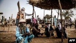 Un pasteur Fulani et son fils portant un turban attendent les transactions de bétail au marché aux bestiaux d'Illiea, dans l'État de Sokoto, au Nigéria, le 21 avril 2019.