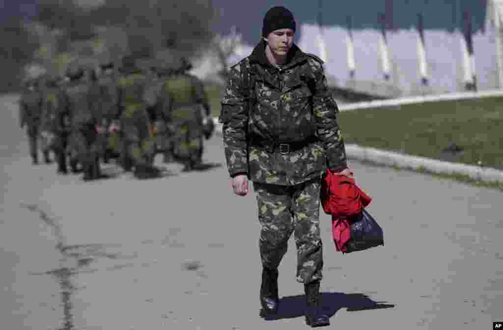 A Ukrainian soldier walks past Russian soldiers marching to their camp outside a military base in Perevalne, Crimea, March 21, 2014.