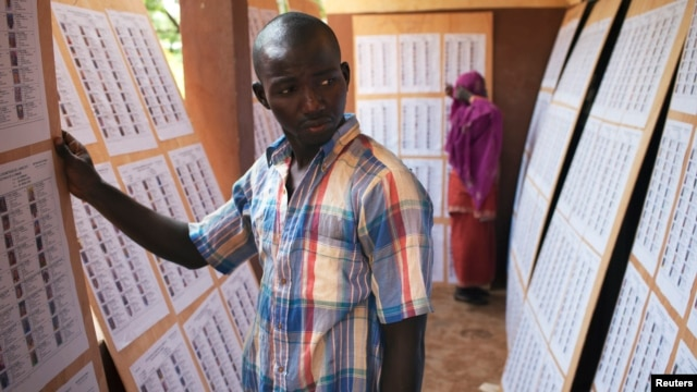 A man searches for his name on a list of eligible voters at an election center in Bamako, July 23, 2013.