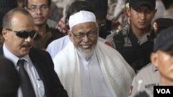 Ulama radikal Abu Bakar Ba'asyir meninggalkan pengadilan Jakarta Selatan setelah divonis 15 tahun penjara (16/6).