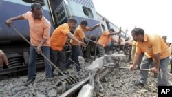 Railway workers remove a damaged slab from the track after a passenger train derailed in Bangapara village near the northeastern city of Guwahati, India, February 3, 2012.