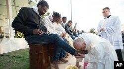 Le pape François embrasse le pied d'un homme pendant le rituel du lavement des pieds au centre de réfugiés Castelnuovo di Porto, à 30km (18, 6 miles) de Rome, 24 mars 2016.