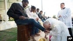 Le pape François embrasse le pied d'un homme lors du rituel du lavage des pieds au centre des réfugiés de Castelnuovo di Porto, à environ 30 km de Rome, le 24 mars 2016.
