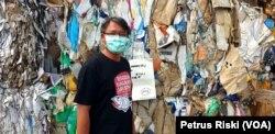 Andreas dari Ecoton dengan latar belakang tumpukan sampah kertas dari Inggris, 28 Juni 2019. (Foto: Petrus Riski/VOA)