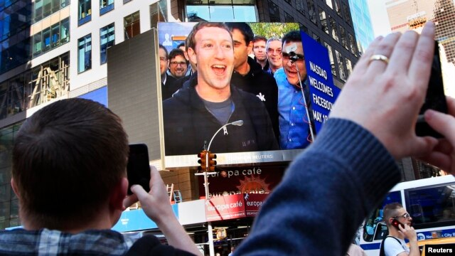 FILE - Facebook Inc. CEO Mark Zuckerberg is seen on a screen televised in New York from the company's headquarters in Menlo Park, California.