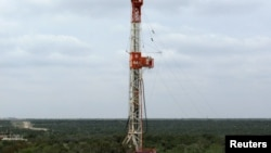 FILE - A rig drills a horizontal well in a search for oil and natural gas in the Wolfcamp shale located in the Permian Basin in West Texas, U.S.