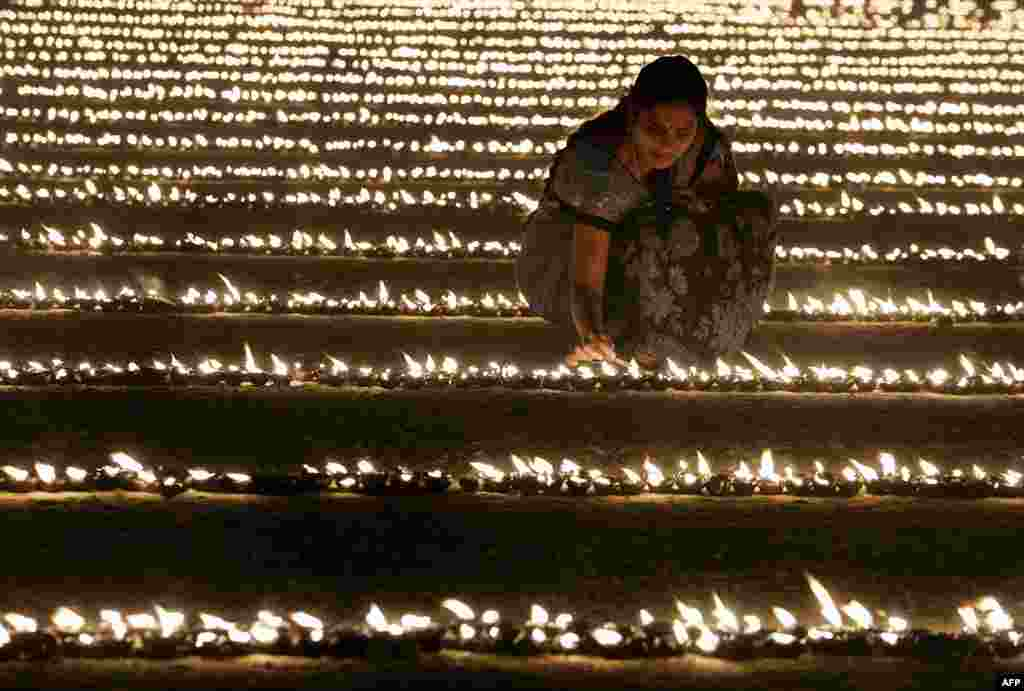 "A Hindu devotee lights oil lamps as part of ""Laksha Deepotsava"" (celebration of a hundred thousand lights), during the Makara Sanranti Festival in Bangalore. Makar Sankranti is a festival celebrated in almost all parts of India, Nepal and Bangladesh in many cultural forms."