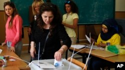 A woman casts her vote at a polling station during municipal elections in Beirut, Lebanon, May 8, 2016. Residents of the capital city are electing a 24-seat municipal council to run the its affairs for the next six years.