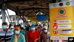 """Penumpang feri mengenakan masker di tengah pandemi COVID-19, berjalan melewati poster """"Hentikan COVID-19"""" di dermaga Pansodan, Yangon, Myanmar. (AP)"""