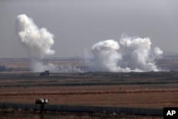 In this photo taken from the Turkish side of the border between Turkey and Syria, in Akcakale, Sanliurfa province, southeastern Turkey, smoke billows from targets inside Syria during bombardment by Turkish forces Thursday, Oct. 10, 2019.