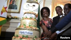 FILE: Zimbabwean President Robert Mugabe (R) is helped by his wife Grace (L) and son Chatunga (C) to cut a cake to celebrate his 92nd birthday at State House in Harare, Feb. 22, 2016.