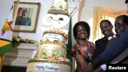 Presiden Zimbabwe Robert Mugabe (kanan) didampingi istrinya Grace (kiri) dan puteranya Chatunga (tengah) memotong kue ulang tahun ke-92 dalam perayaan di State House, Harare (22/2).