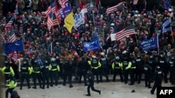 Police hold back supporters of US President Donald Trump as they gather outside the US Capitol's Rotunda on January 6, 2021, in Washington, DC. - Demonstrators breeched security and entered the Capitol as Congress debated the a 2020 presidential election