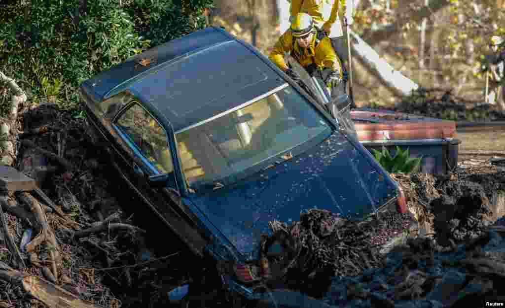 کمک امدادگران برای بیرون آوردن خودرویی که بر اثر رانش زمین در گل فرو رفته است. رانش زمین و هجوم گل و لای به خانههای مردم در کالیفرنیا، خسارتهای زیادی به بار آورد