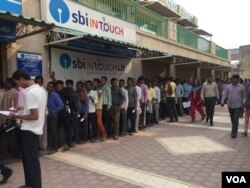 People wait in line to withdraw cash. (Photo: A. Pasricha)