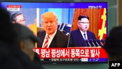 FILE - People watch a television news screen showing pictures of U.S. President Donald Trump and North Korean leader Kim Jong Un at a railway station in Seoul, Nov. 29, 2017.