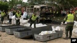 Polisi Kolombia membawa tas-tas berisi korban tewas dalam bus yang terbakar di kota Fundacion, Minggu (18/5).