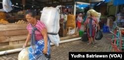 """Perempuan kuli panggul mendapat upah dengan membawa puluhan kilogram barang milik pembeli atau pedagang di Pasar Legi Solo Jawa Tengah, Kamis, 7 Maret 2018. Mereka perempuan perkasa yang jadi """"tulang punggung"""" keluarga. (Foto: Yudha Satriawan/VOA)"""