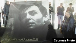 Friends hold up a poster of Syrian filmmaker Naji Jerf, who was gunned down Dec. 27, 2015, in Turkey.