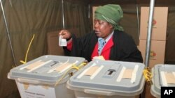 FILE - A woman casts her vote in presidential and parliamentary elections in Zimbabwe's capital, Harare, July, 31, 2013. Four women are among the presidential candidates seeking election on Monday.