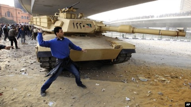 An opposition supporter throws a rock in front of a tank during rioting with pro-Mubarak demonstrators near Tahrir Square in Cairo, February 3, 2011