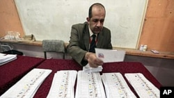 투표용지를 세고 있는 알렉산드리아 시 투표소의 사무원.