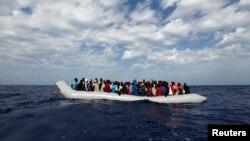 Di dân ngồi chật cứng trên chiếc xuồng cao su chờ đợi được giải cứu ngoài khơi bờ biển Libya.