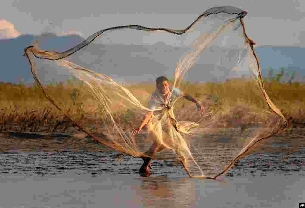 8月30日:一名印度村民在布拉马普特拉河撒下鱼网。